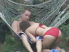 Зрелая дачница в красном бикини в саду балдеет от любительского секса в гамаке