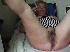 Широкобёдрая зрелая дама курит во время любительской мастурбации волосатой щели