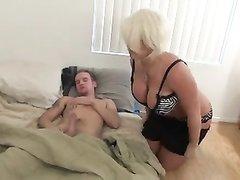 Зрелая блондинка с большими сиськами дрочит и сосёт член молодого любовника