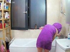 Молодая девушка перед домашней скрытой камерой купается в ванной