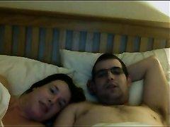 Жена пристаёт к очкастому мужу в постели требуя супружеского секса перед сном
